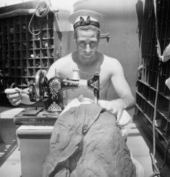 A British sailor uses a sewing machine to repair a signal flag on board the armed merchant cruiser HMS ALCANTARA en route to Sierra Leone, 1942. By Cecil Beaton. Crown Copyright: IWM (CBM 1049).